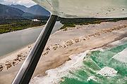 Aerial view: Hollyford River meets Tasman Sea coast in Fiordland National Park. We flew from Milford Sound to Martins Bay to start the Hollyford Track, in Southland region, South Island of New Zealand. We enjoyed an easy 3-day version of the Hollyford Track: Day 1: fly from Milford Sound to Martins Bay, walk to its oceanfront Hut, and see New Zealand fur seals. Day 2: jetboat on Lake McKerrow to Pyke River Confluence, hike to Hidden Falls Hut for overnight lodging. Day 3: tramp out to Hollyford Road end to our prearranged car shuttle. In 1990, UNESCO honored Te Wahipounamu - South West New Zealand as a World Heritage Area.