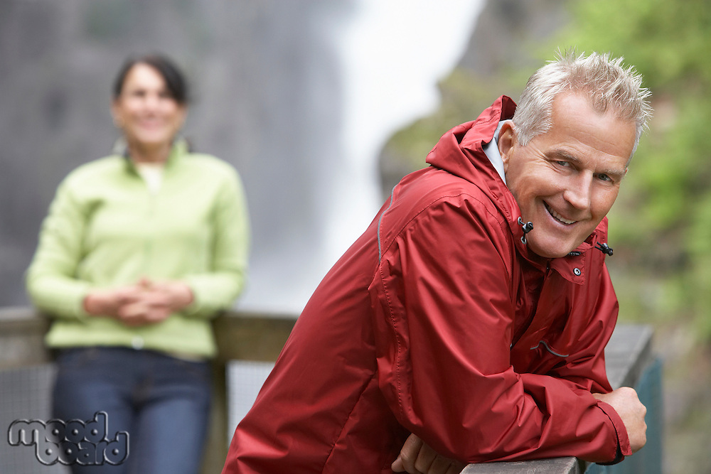 Man and woman in mountains focus on man leaning on railing