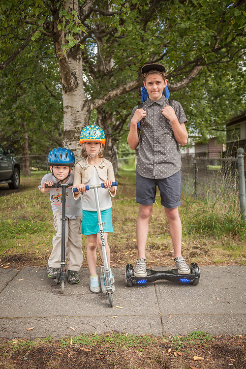 Seven year old Jake and Gracey with their fourteen year old brother, Ben Breun, on his Smart Balance Wheel in Anchorage's South Addition neighborhood.