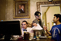 "Farah Qadri, manager of the Diamond Palace nightclub, helps an employee, right, with selling his car, in the office, in Fremont, Ca., on Saturday, March 28, 2009. ""They are like our children, these boys.""."