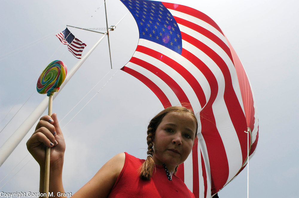 Southampton, NY - 070403 - Katie Burke, 8, from Glen Rock, NJ enjoys a lollipop underneath a large American Flag during the July 4th parade in Southampton, NY Friday morning.   Gordon M. Grant Photo