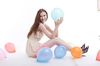 Beautiful young woman in dress on floor with balloons against white background