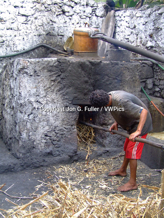 A man stokes the fire with sugar cane leaves to distill grogue, a local alcoholic liquor, from crushed sugar cane.  Valley of Paul, Santo Antao, Republic of Cabo Verde, Africa.