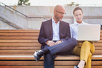 Portrait of businessman and businesswoman sitting on bench while discussing plans