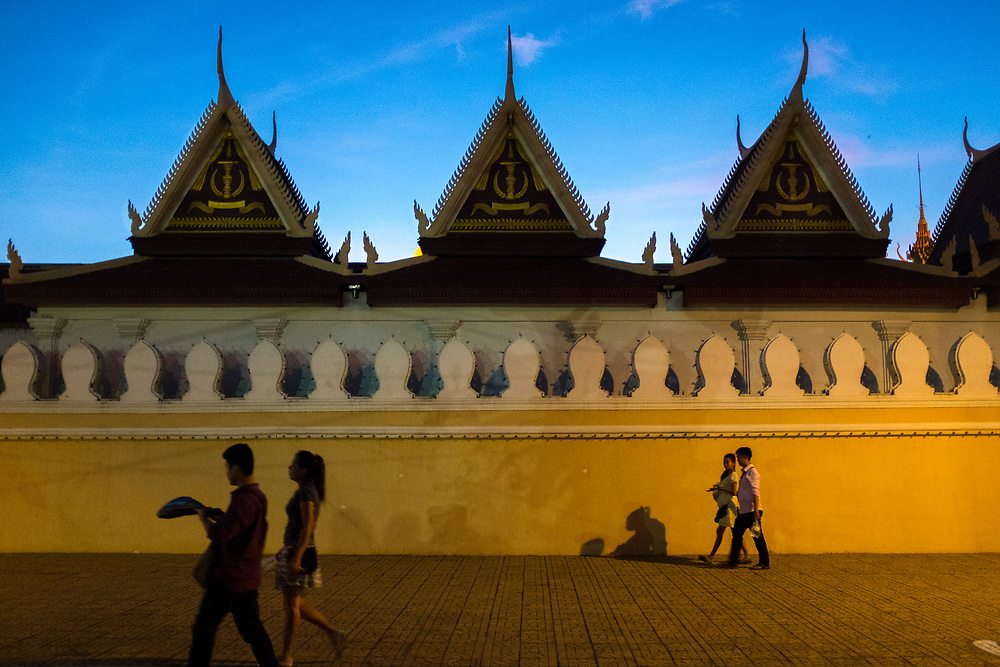 People walking in the shadow of the silver pagoda walls in Phnom Penh, Cambodia. <br /> Photo by Lorenz Berna