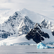 Large mountains rise up from the shore of the Gerlache Straigt on the western side of the Antarctic Peninsula, as a small blue iceberg floats past in the foreground.