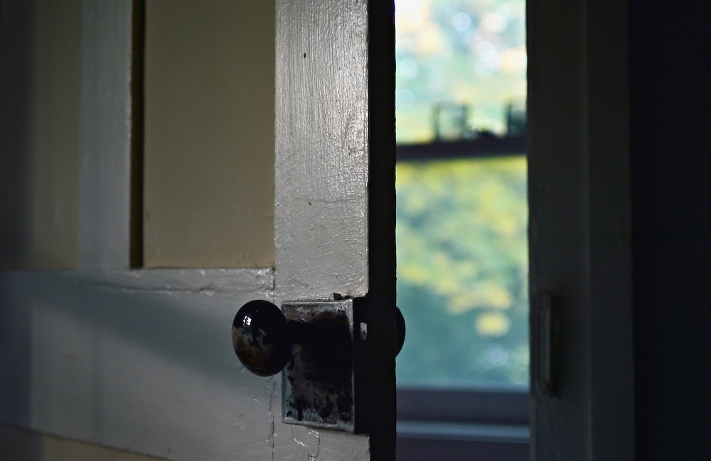 Old wood door and door knob with window behind