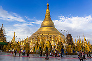 15 JUNE 2013 - YANGON, MYANMAR:  People walk around Shwedagon Pagoda in Yangon. Shwedagon Pagoda is officially known as Shwedagon Zedi Daw and is also called the Great Dagon Pagoda or the Golden Pagoda. It is a 99 metres (325ft) tall pagoda and stupa located in Yangon, Burma. The pagoda lies to the west of on Singuttara Hill, and dominates the skyline of the city. It is the most sacred Buddhist pagoda in Myanmar and contains relics of the past four Buddhas enshrined: the staff of Kakusandha, the water filter of Ko??gamana, a piece of the robe of Kassapa and eight strands of hair fromGautama, the historical Buddha. The pagoda was built between the 6th and 10th centuries by the Mon people, who used to dominate the area around what is now Yangon (Rangoon). The pagoda has been renovated numerous times through the centuries. Millions of Burmese and tens of thousands of tourists visit the pagoda every year, which is the most visited site in Yangon.  PHOTO BY JACK KURTZ