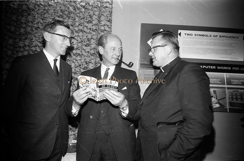"""17/05/1966<br /> 05/17/1966<br /> 17 May 1966<br /> Book reception for """"Decades of Glory: A Comprehensive History of the National Game"""" by Raymond Smith.<br /> This reception was held in the offices of W.D. & H.O. Wills to honour the well known author and journalist, Raymond Smith. His book on the history of Hurling (""""Decades of Glory"""") has just been published with the assistance of Wills of Dublin and Cork and the Central Council of the G.A.A.<br /> Picture shows (from left to right): Raymond Smith (author), Jack Lynch (at the time he was the Minister for Finance), and Rev. Fr. Murray."""