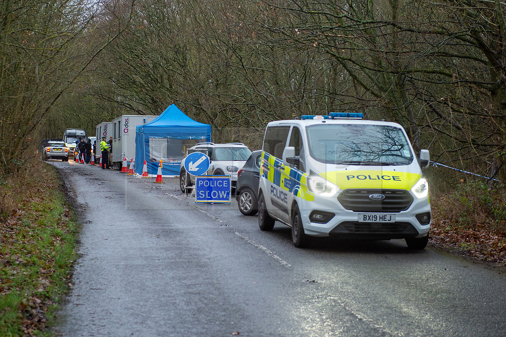 """© Licensed to London News Pictures. 10/12/2019. Gerrards Cross, UK. Police vehicles and portable cabins line Hedgerley Lane as the  Metropolitan Police Service continues a search of woodland in Gerrards Cross, Buckinghamshire. Police have been in the area conducting operations on Hedgerley Lane since Thursday 5th December 2019. In a press statement issued on 7th December a Metropolitan Police spokesperson said """"Officers are currently in the Gerrards Cross area of Buckinghamshire as part of an ongoing investigation.<br /> """"We are not prepared to discuss further for operational reasons."""" No further updates have been issued as of 10th December. Photo credit: Peter Manning/LNP"""