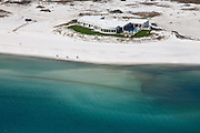 An isolated beach mansion sits exposed to the open ocean.  Barrier dunes protect the shoreline from harsh storms and are a habitat for many seaside organisms.  Houses are at greak risk when placed on the shoreline in front of protected dunes.
