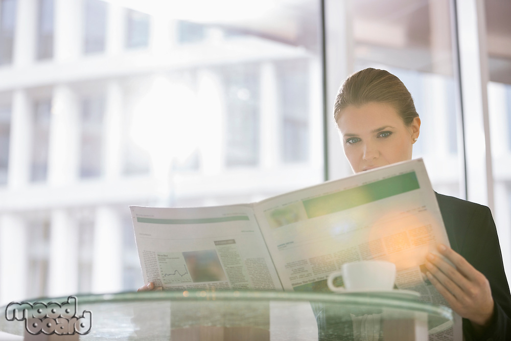 Businesswoman reading newspaper at office cafe