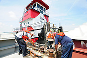 {8/24/12} {10pmCST} -JOB # 42286- Greenville , MS, U.S.A. --Workers for Wepfer Marine of Greenville MS. tie barges together and then tether tehm to shore, in a big holding pattern alomg the bansk of the Mississsippi RIver beacuse the water level is causing a back up of barge traffic.  Historically low river levels on the Mississippi River are causing havoc on river traffic: grounding barges loaded with grain and fertilizer, traffic jams several miles long and forcing the Coast Guard to close down chunks of the river due to groundings. The area around Greenville, Miss., has closed three times the past week due to groundings. Last year, there were five total groundings the entire low-water season. Locals who fought historic high-water floods last year are this year engaged in a different fight: keeping barges afloat on a vanishing Mississippi.  -- Photo by Suzi Altman, Freelance..