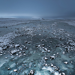Frozen river with snow in wintertime, Iceland.