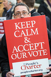 PLACE, January 14 2018. A few dozen protesters from 'The People's Charter' group demonstrate outside Downing Street demanding that the Brexit referendum result is respected following calls for a second referendum. PICTURED: A man peers over his placard. © Paul Davey