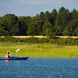 A woman kayaks near the mouth of the Connecticut River in Old Lyme, Connecticut.  The Nature Conservancy's Griswold Point Preserve.  Long Island Sound.