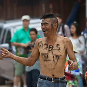 "An intoxicated Thai man has his body painted with the word ""Buffalo"" during festivities at Thailand's Phi Ta Khon Ghost festival Friday, June, 22nd, 2012, in Dan Sai, Thailand.  The Dan Sai Ghost Festival is unique to the Isan area of Thailand in the east and is part of local beliefs in spirits and ghost and is also a Buddhist merit making festival.  The ghost masks are made from bamboo sticky rice cookers and the costumes usually strips of cloth sewn together.  The origins of the Phi Ta Khon Festival are said to come from Buddha's last great incarnation before attaining Enlightenment."