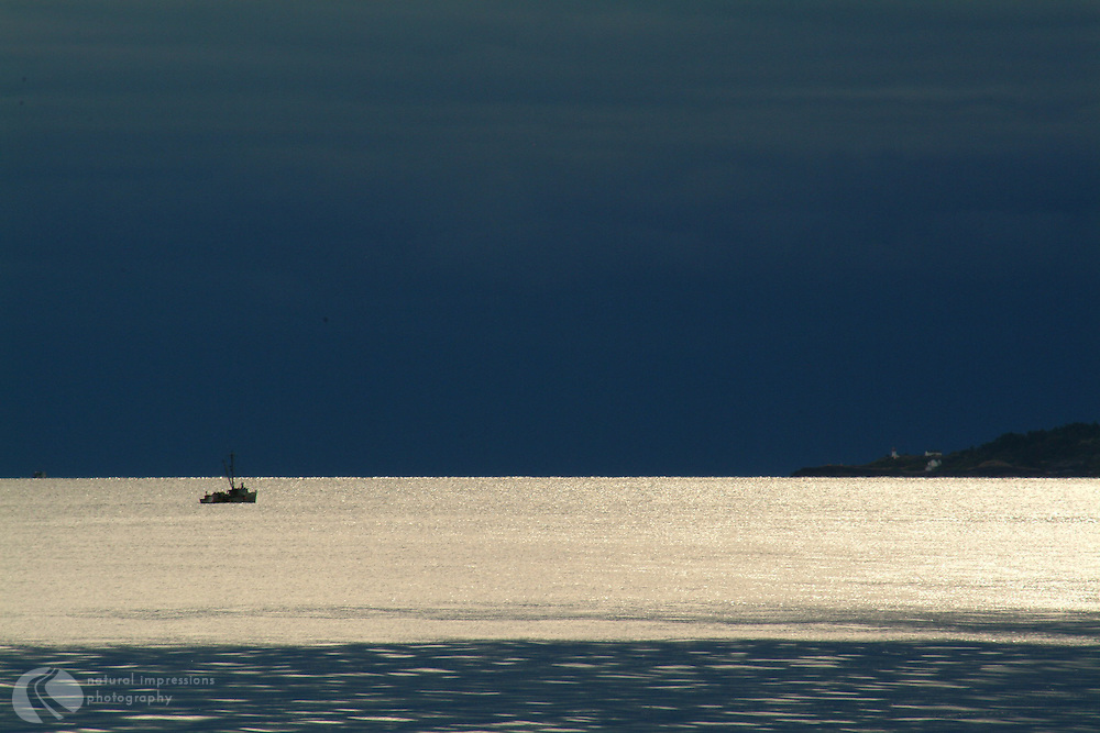 Just off Quadra Island, near Campbell River on Vancouver Island, a lone fisherman guides his boat through the Straits of Georgia.