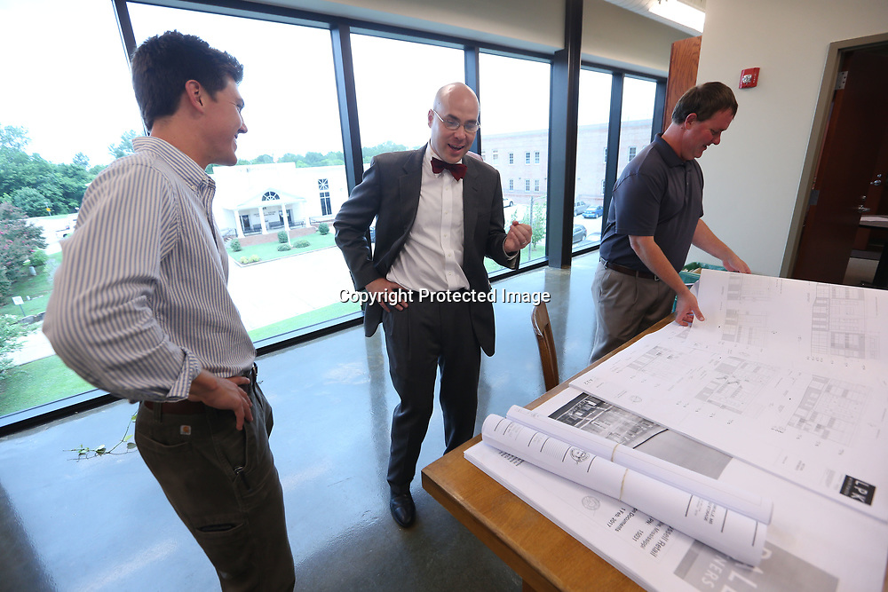 Outgoing Starkville Mayor Parker Wiseman, center, talks with Cody Burnett, left, assistant city engineer, and Daniel Havelin, City Planner as they look over plans for an upcoming building project.