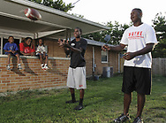 Terry Talbott, Jr. (right) and his brother Terrence pass a football with a friend, watched by (from left) Devoni'ye Benson, 6; mother Natasha White and DeMorea Benson, 7,  Sunday August 12, 2007.