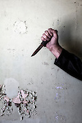 a male hand with a rusty knife