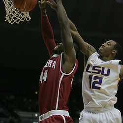 Jan 09, 2010; Baton Rouge, LA, USA; LSU Tigers guard Aaron Dotson (12) blocks a dunk attempt by Alabama Crimson Tide forward Chris Hines (44) during the second half at the Pete Maravich Assembly Center. Alabama defeated LSU 66-49.  Mandatory Credit: Derick E. Hingle-US PRESSWIRE