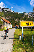 Cyclists entering the village of Ribjek, Slovenia