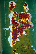 Abstract rust pattern appear on a iron sheet painted a dark green colour
