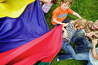 "Shaylie Corbey, 7, is dragged away from the ""sharks"" attacking from under a parachute by her friends Zane Pomerantz, top, Ryland Hoit, right, and Alexandra Plucker, bottom right, during a game Tuesday of ""sharks and lifeguards"" at McEuen Park. Students from Sorensen Magnet School students spent the day at the park as classwork and events before summer vacation wind down."
