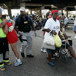 A Emergency Medical Technician holds a scared victim of the hurricane as others rush to board a helicopter during a helicopter pickup at the Causeway on Interstate 10 during the aftermath of Hurricane Katrina Friday, September 2, 2005 in New Orleans, Louisiana.  <br /> (Pasadena Star-News Keith Birmingham)