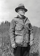 Gordon MacQuarrie wearing a fringed buckskin jacket, at Little Bass Lake, WI, 1928.