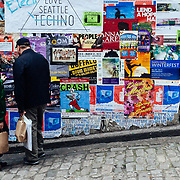 Two men view posters along a wall in downtown Seattle, Washington.
