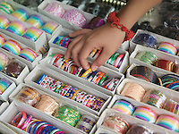 Young woman looking at different bracelettes on display close-up on hand