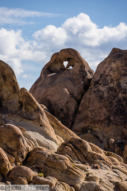 Heart Arch, BLM Alabama Hills Recreation Area, on the eastern slope of the Sierra Nevada Mountains in the Owens Valley, west of Lone Pine in Inyo County, California, USA. The Alabama Hills are a popular filming location for television and movie productions (such as Gunga Din, Gladiator, Iron Man,  Transformers: Revenge of the Fallen), especially Westerns (Tom Mix films, Hopalong Cassidy films, The Gene Autry Show, The Lone Ranger, Bonanza, How the West Was Won, and Joe Kidd). Two main types of rock are exposed at Alabama Hills: 1) orange, drab weathered metamorphosed volcanic rock 150-200 million years old; and 2) 82- to 85-million-year-old biotite monzogranite which weathers to potato-shaped large boulders.
