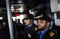 "VALLETTA, MALTA - 8 FEBRUARY 2017: Two petty officials of the Libyan Navy Coastguard are seen here in the pilot house of the San Giorgio, an amphibious transport dock of the Italian Navy, as it sets out of the harbor of Valetta, Malta, on Febuary 8th 2017.<br /> <br /> As a consequence of the April 2015 Libya migrant shipwrecks, the EU launched a military operation known as European Union Naval Force Mediterranean (EUNAVFOR Med), also known as Operation Sophia, with the aim of neutralising established refugee smuggling routes in the Mediterranean. The aim of this new operation launched by Europe is to undertake systematic efforts to identify, capture and dispose of vessels as well as enabling assets used or suspected of being used by migrant smugglers or traffickers. On 20 June 2016, the Council of the European Union extended Operation Sophia's mandate reinforcing it by supporting the training of the Libyan coastguard.<br /> Thus far, following EUNAVFOR MED operation Sophia's activities, 101 suspected smugglers and traffickers have been apprehended and transferred to the Italian<br /> authorities and 380 boats were removed from the criminal organizations' availability. The Operation has saved 32.081 migrants, among whom 1888 children.<br /> <br /> On February 2nd 2017 Italian Premier Paolo Gentiloni and Prime Minister of the U.N. backed Libyan government Fayez al-Serraj signed a memorandum of understanding on cooperation to combat illegal migration, human trafficking and contraband and on reinforcing the border between Libya and Italy. The following day, as EU leaders meet in Malta for a summit, European Council President Donald Tusk said after talks with Serraj, that ""it is time to close the (migrant) route from Libya to Italy"" and that ""the EU has shown it is able to close the routes of irregular migration, as it has done in the eastern Mediterranean.""  Tusk said the Central Mediterranean route was ""not sustainable either for the EU or for Libya"", where he said traffickers were under"