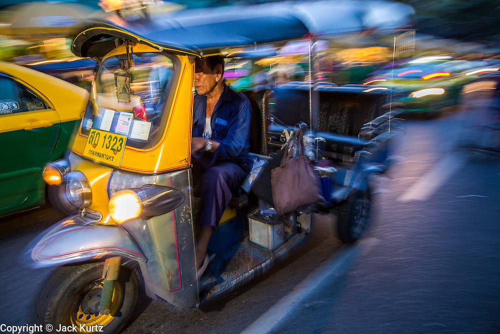 19 OCTOBER 2012 - BANGKOK, THAILAND:  A tuk-tuk (three wheeled taxi common in developing cities in Asia) drives through the Bangkok Flower Market. The Bangkok Flower Market (Pak Klong Talad) is the biggest wholesale and retail fresh flower market in Bangkok.  The market is busiest between 3:30AM and 6AM. Thais grow and use a lot of flowers. Some, like marigolds and lotus, are used for religious purposes. Others are purely ornamental.          PHOTO BY JACK KURTZ