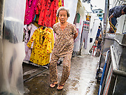30 MAY 2013 - BANGKOK, THAILAND:  An elderly woman walks through Bobae Market in Bangkok. Bobae Market is a 30 year old famous for fashion wholesale and is now very popular with exporters from around the world. Bobae Tower is next to the market and  advertises itself as having 1,300 stalls under one roof and claims to be the largest garment wholesale center in Thailand.    PHOTO BY JACK KURTZ