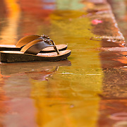 A woman's sandals sit in water during Ganga aarti along the banks of the Ganges River at Triveni Ghat, Rishikesh, Uttarakhand, India.