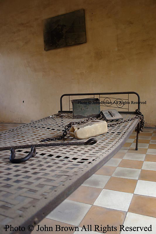"""A bed and torture devices used by the Khmer Rouge to interrogate prisoners during the Pol Pot regime are depicted in Building """"A"""" at Tuol Sleng Genocide Museum in Phnom Penh, Cambodia. Building """"A"""" contains three stories divided into 20 cells.  The first story has 10 cells used for jailing, interrogating, and torturing the prisoners who had been high officials. The second and third floors have 5 big cells each used for the same purpose."""