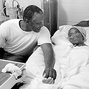 Aaron Washington, left, sits with Jimmie Burnett as Jimmie's health worsens. Washington, also an inmate at Angola Prison, is considered one of Jimmie's inmate family members and is granted special visitation privileges while Jimmie is in hospice care. Jimmie died the day after this photo was taken.