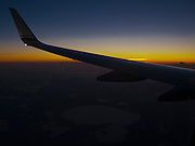 nearing the end of a red eye flight with sunrise in a few minutes - an airplane wing silhouetted against the predawn sky.