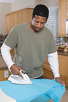 Mid-adult man ironing shirt in domestic kitchen