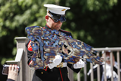 August 26, 2017 - Lyon Township, MI, USA - Cena's handler Jeffrey DeYoung, looks at a metal sculpture of a Marine battle flag made by Marine veteran Laszlo Szalay of Brighton, not pictured, during the memorial service at the Michigan War Dog Memorial in Lyon Township, Mich., on Saturday, August 26, 2017. (Credit Image: © Junfu Han/TNS via ZUMA Wire)