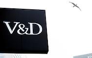 ROTTERDAM - DREESMAN; en; v&amp;d; Vroom; vroom en dreesman in het centrum van rotterdam .Personeel van V&amp;D moet per februari 5,8 procent loon inleveren. Ook worden 50 van de 450 banen op het hoofdkantoor geschrapt. Volgens de warenhuisketen zijn deze maatregelen nodig om de steun van aandeelhouders en banken te houden.<br /> Topman Don Roach van V&amp;D spreekt van &quot;forse maatregelen&quot; die nodig zijn om te overleven in de snel veranderende markt. De bonden laten weten dat de maatregel eenzijdig, zonder overleg, is afgekondigd. V&amp;D heeft een aantal moeilijke jaren achter de rug. Het bedrijf was zoekende naar een werkende strategie en een passend assortiment. Daarnaast hebben veel winkelbedrijven het lastig nu de verkoop via internet sterk toeneemt. Vorig jaar leed het concern een verlies van 42 miljoen euro. <br /> Loonoffer Het komt niet vaak voor dat bedrijven een loonoffer vragen van hun werknemers. Anderhalf jaar geleden kwam automatiseerder Capgemini met een soortgelijke maatregel. Daarbij ging het specifiek om oudere werknemers met een hoger salaris, die moesten inleveren. Er ontstond veel commotie en de maatregel werd ingetrokken.<br /> Openbreken<br /> V&amp;D probeert verder de kosten te drukken door huurcontracten open te breken om zo te proberen de huurkosten te verlagen. <br /> In totaal werken er zo'n 5000 mensen bij V&amp;D. De huidige topman Roach wordt per maart van dit jaar vervangen door John van der Ent, die nu nog de Etam Groep leidt.<br />   COPYRIGHT ROBIN UTRECHT