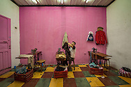 A man works on hemming a pair of pants in  Santa Rosa de Copan, Honduras Oct 11, 2014.