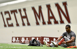 Former Texas A&M running back Trey Williams puts his shoes on before running drills during Texas A&M Pro Day at the McFerrin Athletic Center on Wednesday.