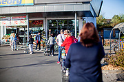People are waiting in front of a shop in Oberursel in times of social distancing because of the corona virus.