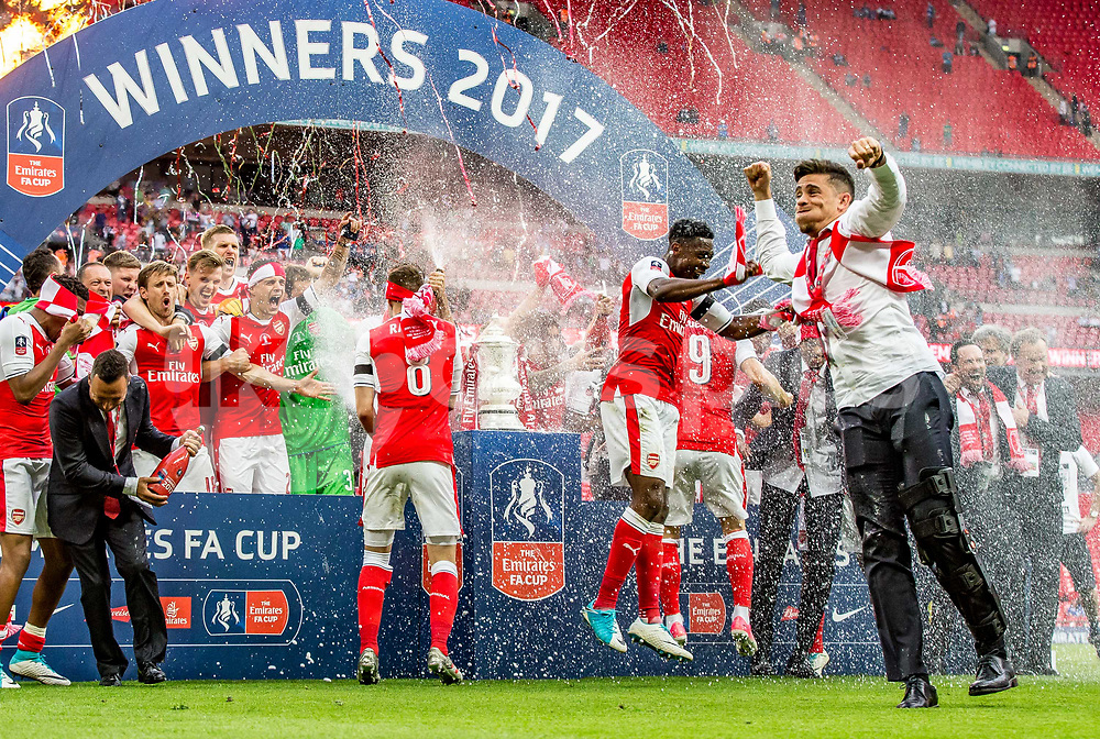 Injured Gabriel Paulista (foreground) jumps for joy of as Arsenal celebrate during the Emirates FA Cup Final between Arsenal and Chelsea at Wembley Stadium, London, England on the 27th May 2017. Photo by Liam McAvoy.