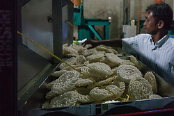May 1, 2019 - Depok, West Java, Indonesia - A man arranges dried kerupuk or crackers after they fry it at a kerupuk factory in Depok, Indonesia, 01 May 2019. Despite the government's decision to declare the International Labor Day that falls on every May 1 as a national holiday, many factories in Indonesia continue to operate in a bid to meet their production target. Workers who fail to show up for work might face serious threats, mainly layoffs. This worsens their already-poor welfare following the poor wage system that sees many workers are paid below minimum wage set by the government. (Credit Image: © Afriadi Hikmal/ZUMA Wire)