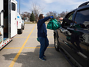 "17 MARCH 2020 - DES MOINES, IOWA: CARRIE LARUE, of the Des Moines Area Religious Council (DMARC) takes bags of food to a family waiting in their car in the parking lot of Carver Elementary School in Des Moines. Des Moines Public Schools are closed for at least 30 days because of the Coronavirus outbreak. Des Moines area religious organizations and food banks are working together to bring free food to children in at risk communities. Volunteers and workers are practicing ""social distancing"" by leaving the food packages on the pavement and recipients pick up the packages. Tuesday, the Governor of Iowa ordered all restaurants and bars to close or go to take out only. The Iowa Department of Public Health has urged all public buildings, like libraries and schools, to close, and all schools in Iowa are closed for at least 30 days.    PHOTO BY JACK KURTZ"